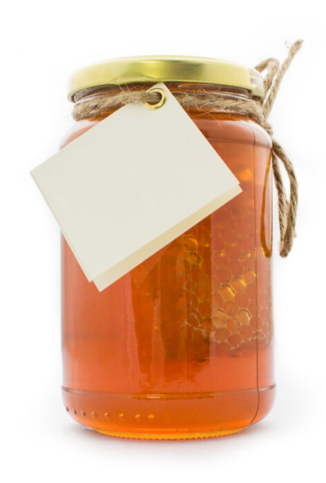 Honey jar filled with honey and a honeycomb